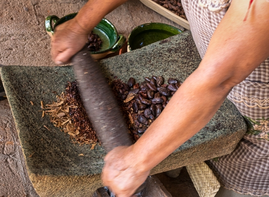 crushing cacao and cinnamon on a metate w a mano